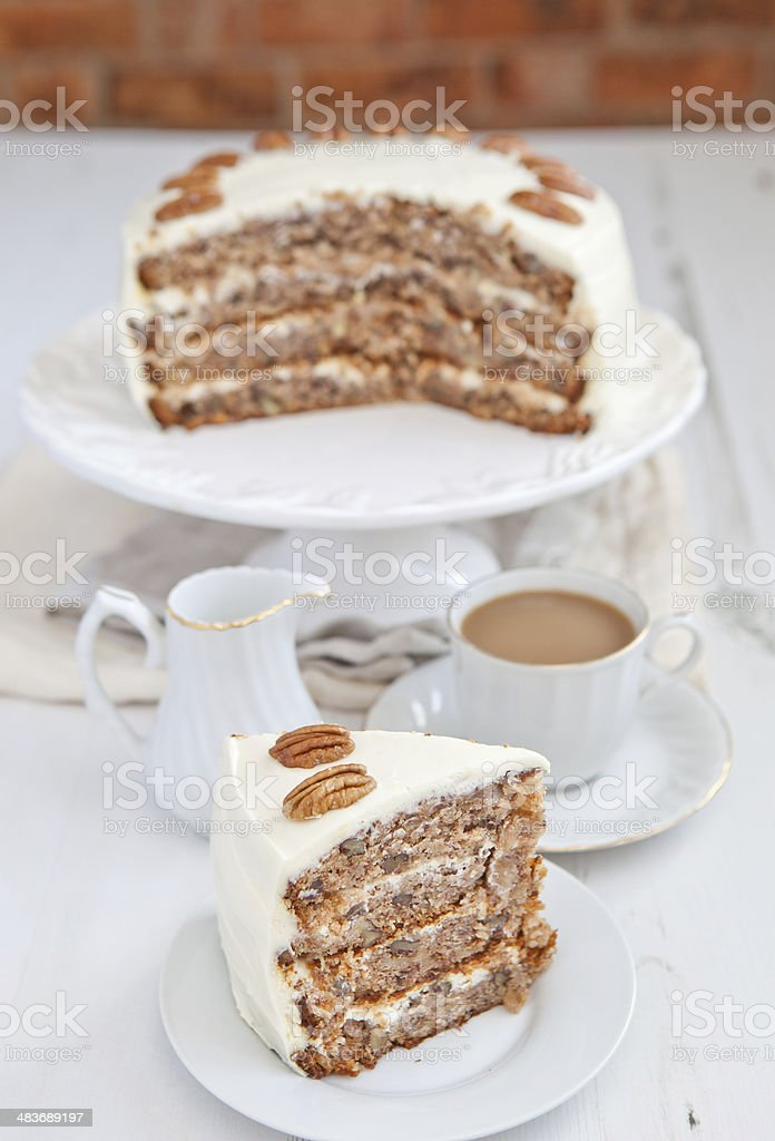 Piece of Hummingbird cake with pecans and cream cheese frosting stock photo