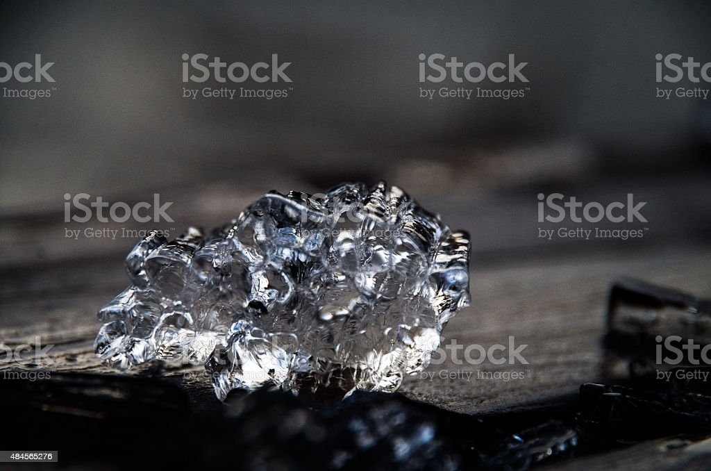 Piece of ice on wood. stock photo
