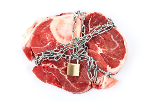 Piece of meat in chains - concept of food shortage and unfair distribution of food
