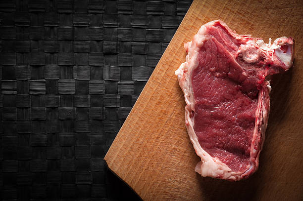 Piece of meat on chopping board stock photo