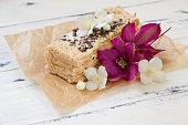 Piece of Napoleon cake decorated flowers.Beautiful dessert.Homemade bakkery,custard creame