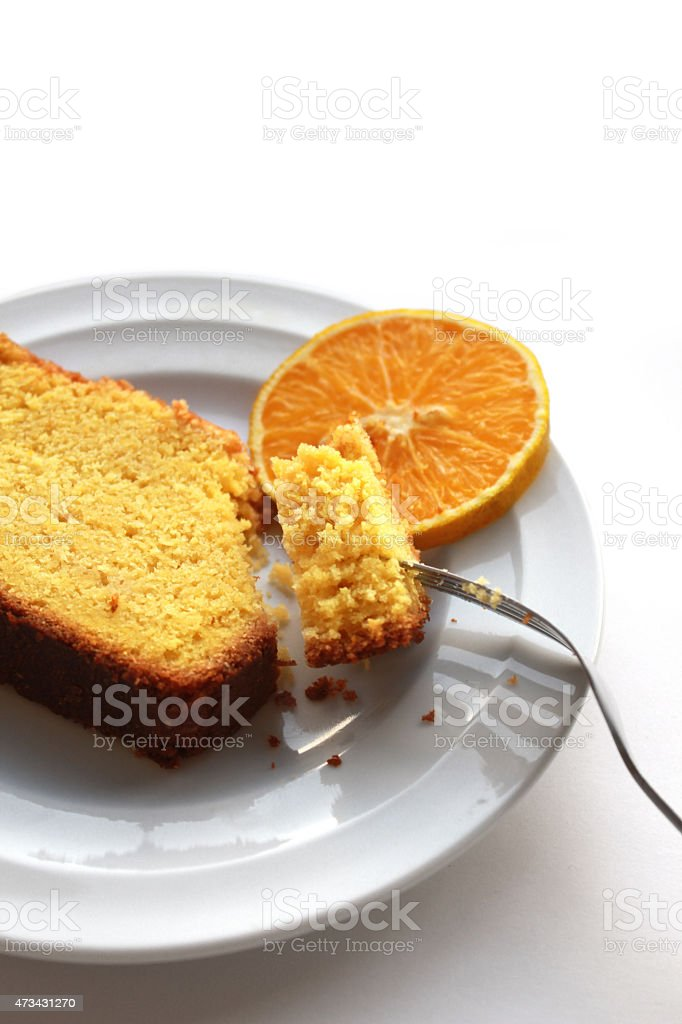 Piece of orange cake, on a white plate with fork stock photo