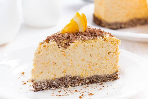 stück orange cheesecake auf einem teller, nahaufnahme - käsekuchen kekse stock-fotos und bilder