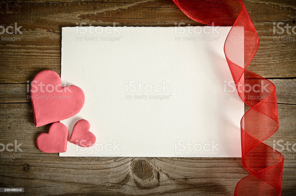 piece of paper with hearts and ribbon stock photo