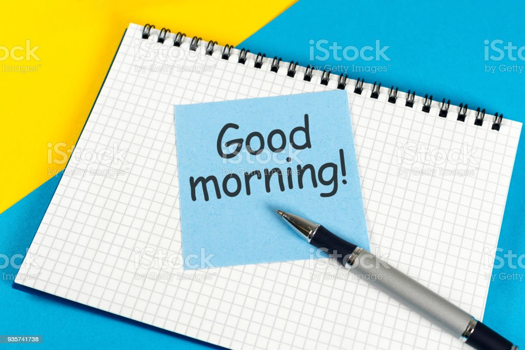 Piece of paper with text Good morning on the yellow-blue table close-up stock photo