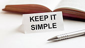 istock piece of paper with text Keep It Simple on the background of books, pens, on a white background 1257460504