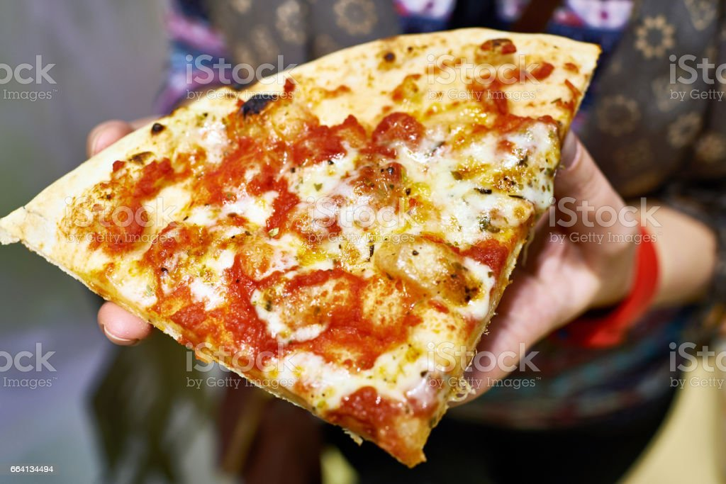 Piece of pizza in hands of woman foto stock royalty-free