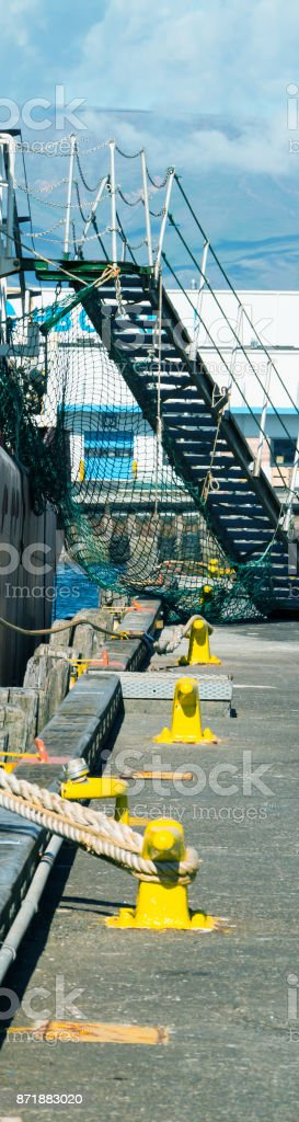 Piece of port with ship, mooring, staicase, tackles and ropes. Wide skyscraper. stock photo