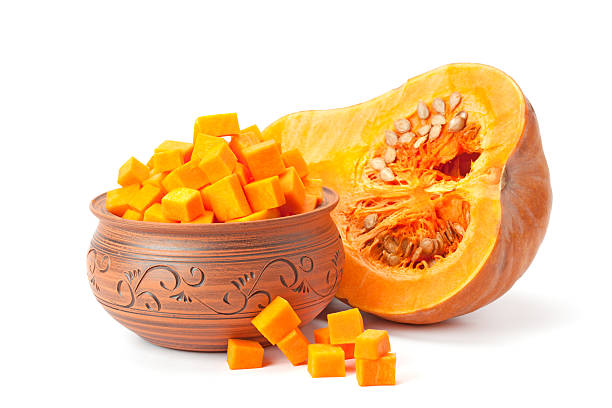 piece of pumpkin,   cubes in a clay pot - crock pot süßigkeiten stock-fotos und bilder