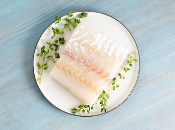 piece of raw cod fish fillet on plate on blue wooden table, top view - cod imagens e fotografias de stock