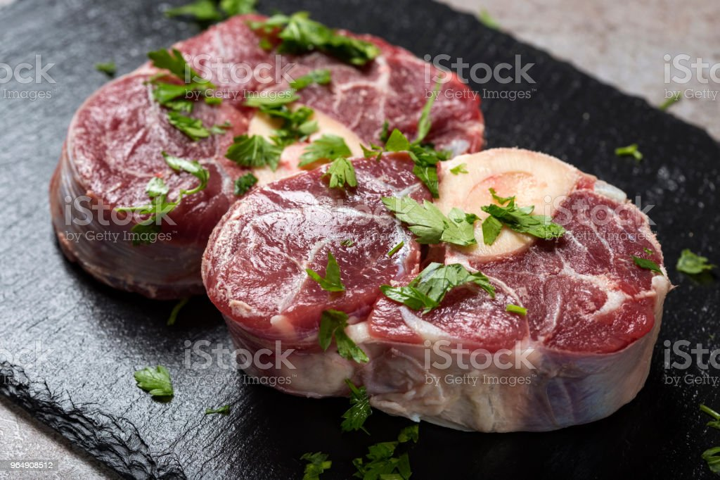 Piece of raw fresh beef shank, lower part of cow's foreleg with fresh green parsley stock photo