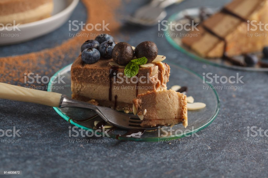 A piece of raw vegan chocolate caramel cheesecake with blueberries, raw almonds and candy beads. Healthy vegan food concept. stock photo