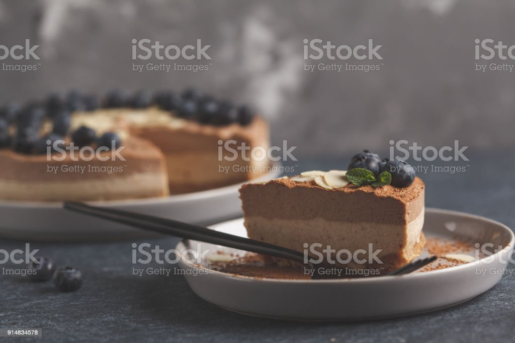Piece of raw vegan chocolate-caramel cheesecake with blueberries and almonds. Healthy vegan food concept. stock photo