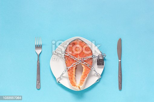 Piece of red fish on plate and chain with closed padlock, fork table-knife on blue background. Concept-prohibition, embargo, danger artificially grown fish or allergy Copy space Flat Lay