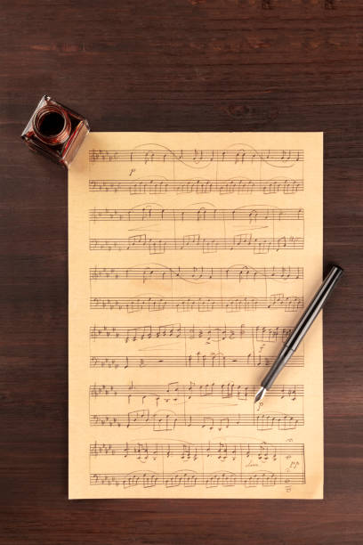 A piece of sheet music, shot from above on a dark rustic wooden background with a nib pen and an ink well stock photo