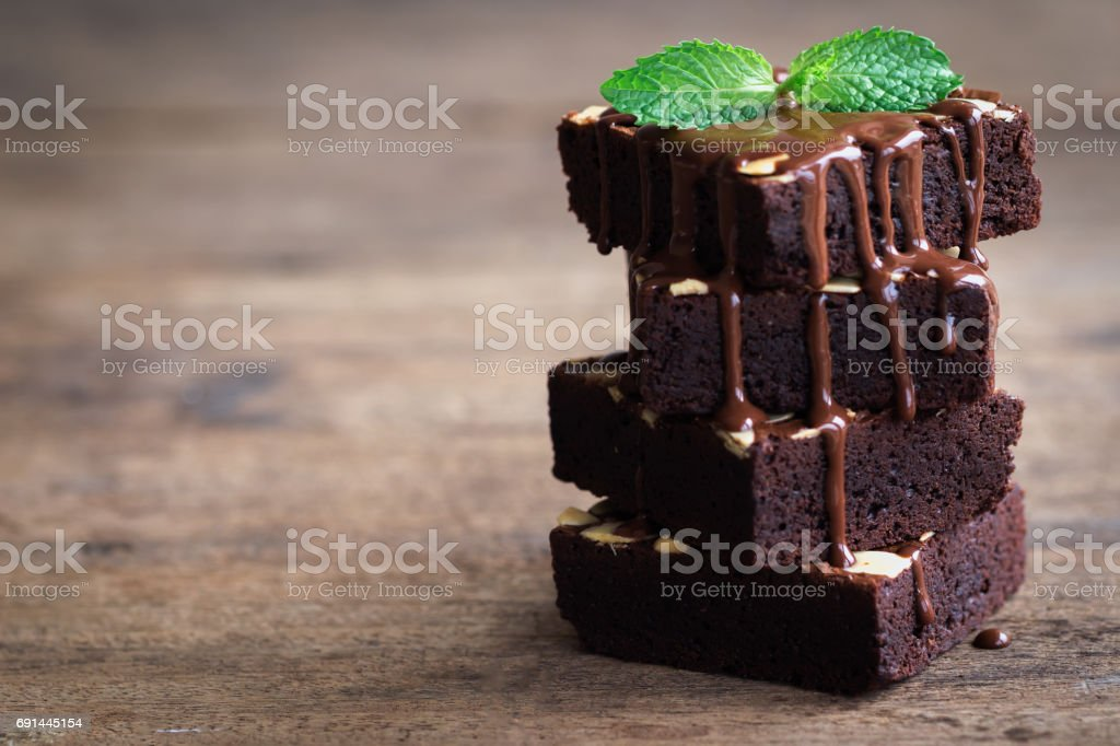 Piece of stack homemade dark chocolate brownies topping with almonds slices and mint on wood table. Bitter,sweet and fudge. - foto stock
