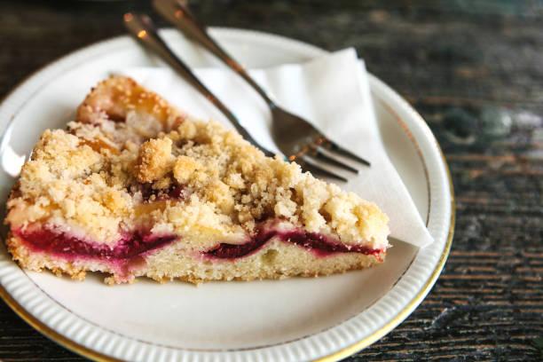 süße kuchen mit dessertgabel auf einem teller auf einer holzfläche im café - himbeer crumble stock-fotos und bilder