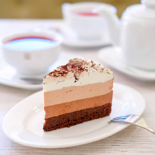 Piece of triple chocolate mousse cake on a white plate in cafe. Sweet dessert concept. stock photo