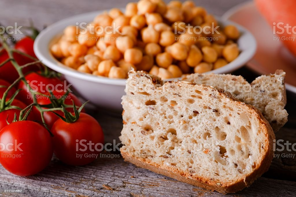 Piece of wholewheat bread with tomatoes and chickpeas stock photo
