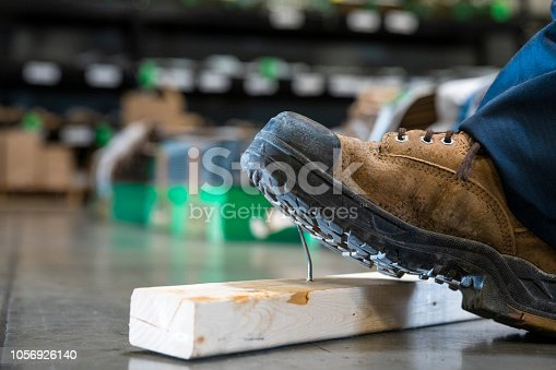 An industrial safety topic. A piece of wood with an exposed nail sticking out and a boot stepping on it.