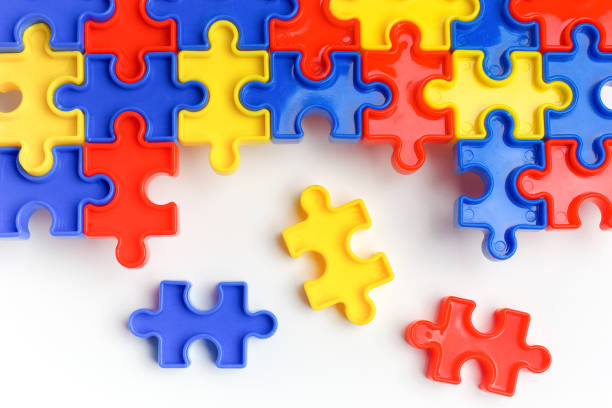 Pieces from a colorful jigsaw puzzle arranged to form a page on white background. Break barriers together for autism concept stock photo