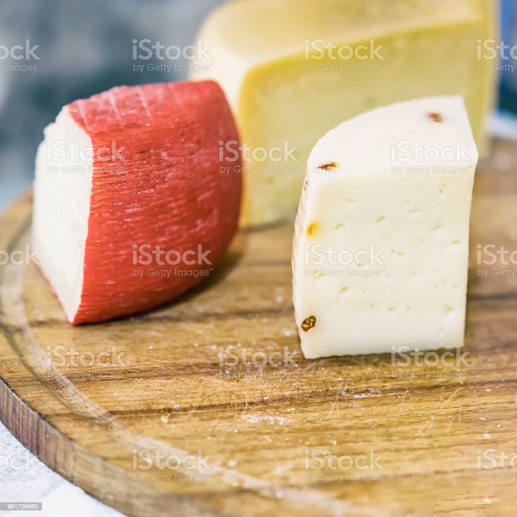 Pieces heads of soft cheeses with different additives on wooden market board. Gastronomic dairy produce, real scene in the food market, square stock photo