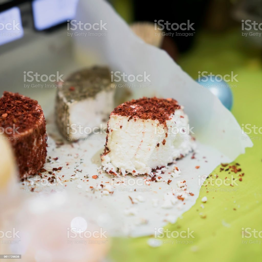 Pieces heads of soft cheeses with different spices and additives on wooden market board. Gastronomic dairy produce, real scene in the food market stock photo