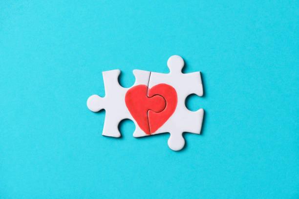 pieces of a puzzle forming a heart - romanticismo concetto foto e immagini stock
