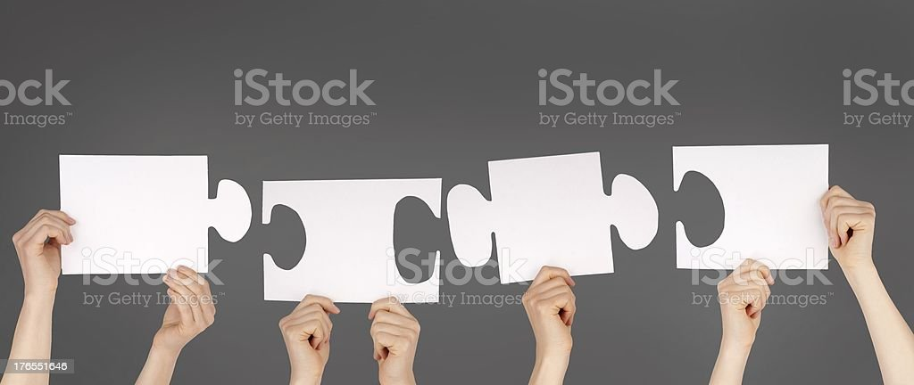 Pieces of a puzzle in white being held up in the air royalty-free stock photo