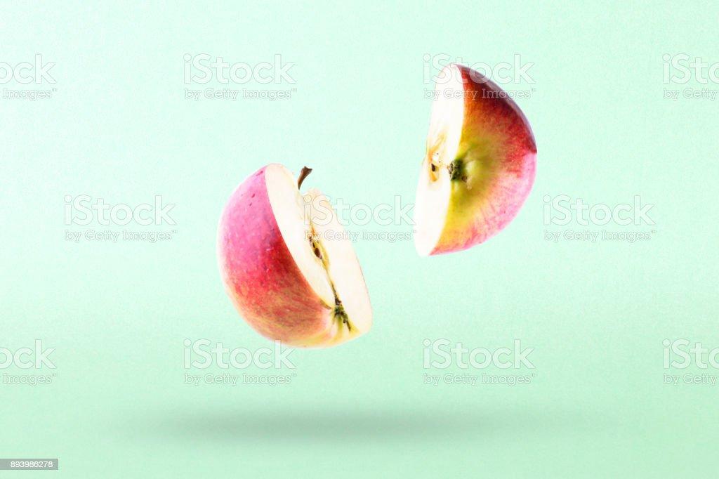 Pedaços de maçã em voo. Metade da aplle no ar - foto de acervo