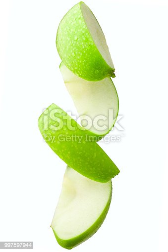 Pieces of an apple in flight on a white background, isolated