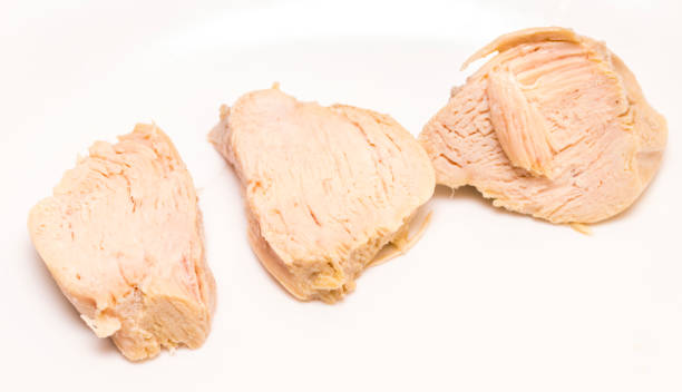 Pieces of boiled chicken breast over white background stock photo