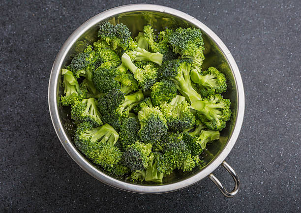 Pieces of broccoli in a sieve stock photo