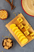 istock Pieces of Canjica or Curau. Tipical brazilian food made from corn. Jerk. In a piece of wood. with a traditional hat. 1201348995