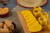istock Pieces of Canjica or Curau. Tipical brazilian food made from corn. Jerk. In a piece of wood. with a traditional hat. 1201349219