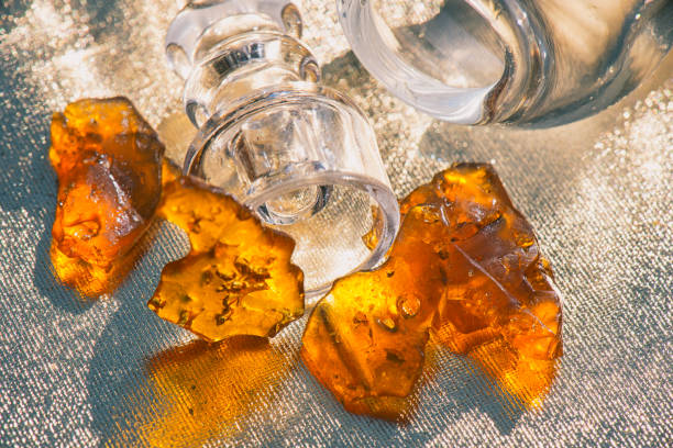 Pieces of cannabis oil concentrate aka shatter with glass rig stock photo