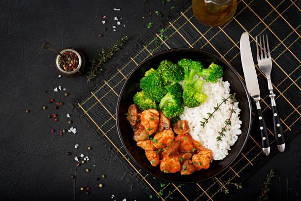 Trozos de filete de pollo con setas estofadas en salsa de tomate con arroz y brócoli hervido. Nutrición adecuada. Estilo de vida saludable. Menú dietético. Vista superior - foto de stock