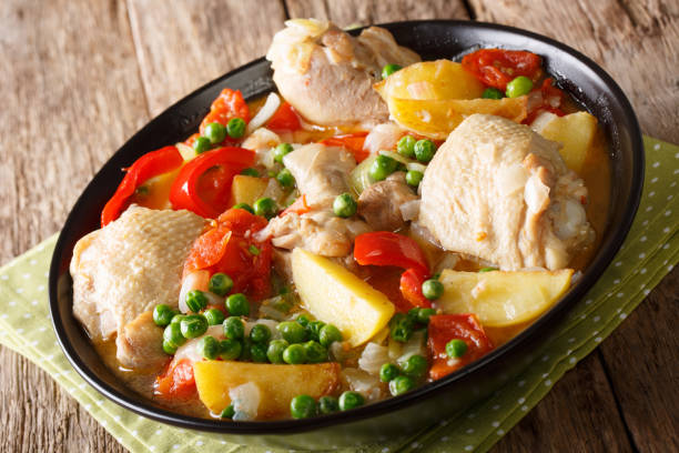Pieces of chicken stew with potatoes, peppers, tomatoes, peas and onions close-up. horizontal stock photo