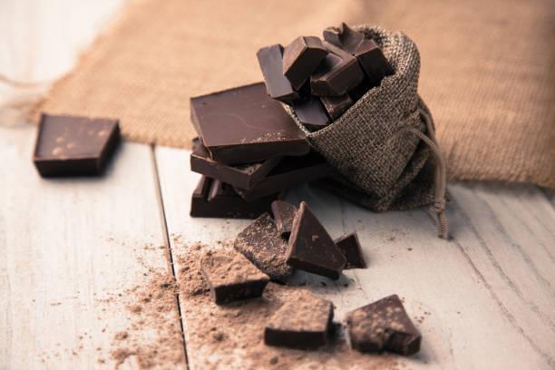 stukken van chocolade in een zak - pure chocola stockfoto's en -beelden