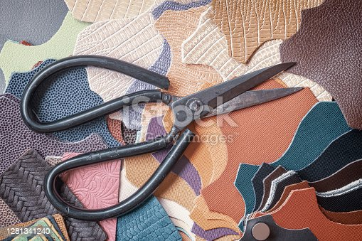 Pieces of colorful leather and scissors, tailoring workshop, workshop, manufacturing of fashion accessories. Top view.