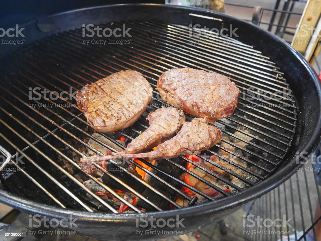 Pieces of cooked steaks on picnic barbecue grill oven waiting to be served. stock photo
