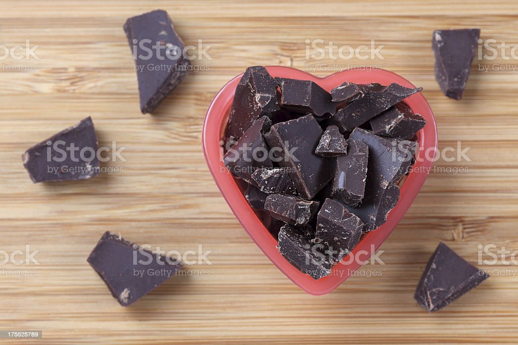Pieces of dark chocolate in a heart bowl stock photo