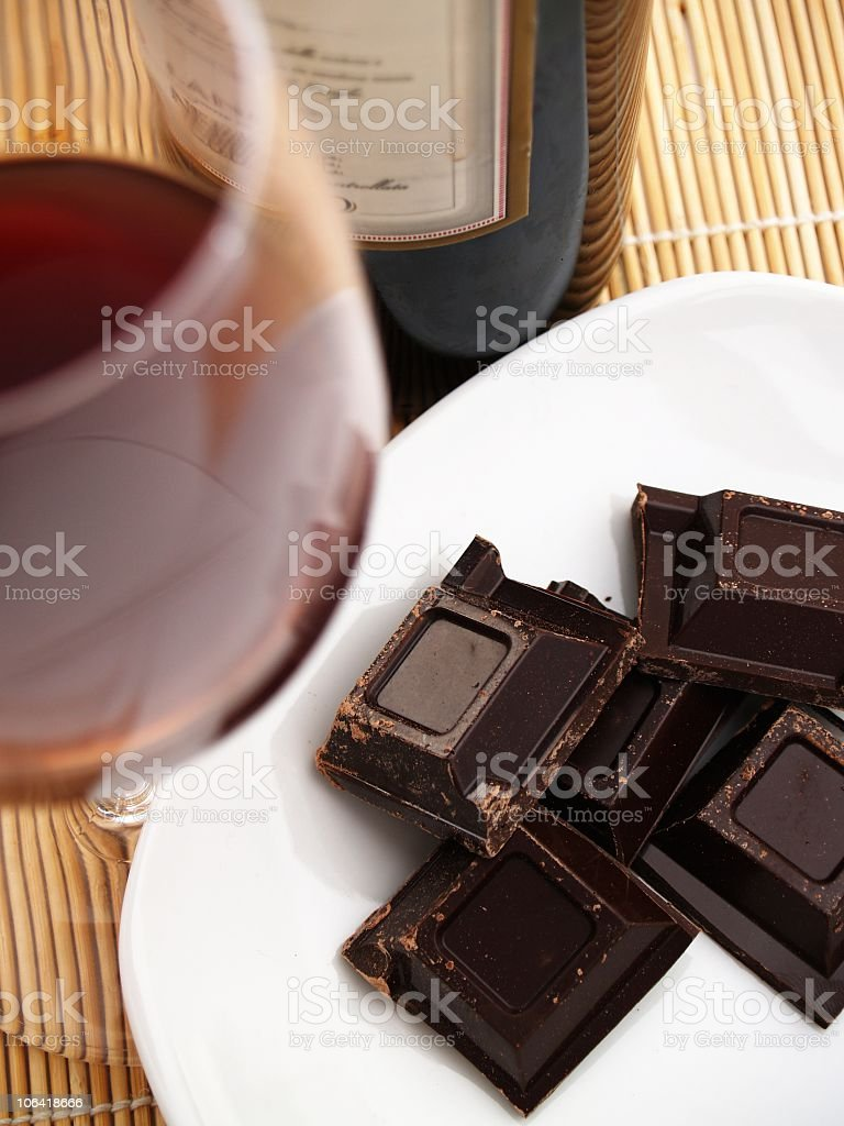Pieces of dark chocolate on a plate served with red wine royalty-free stock photo