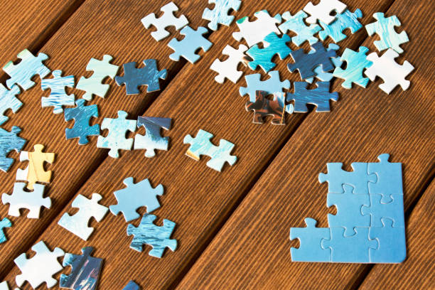 pieces of different puzzles on a wooden table. the concept of thinking development - jigsaw puzzle stock photos and pictures