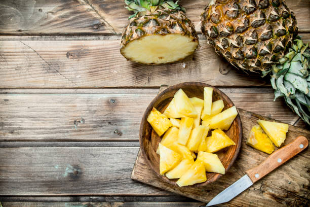pieces of fragrant pineapple in a bowl on a cutting board with a knife. - ananas zdjęcia i obrazy z banku zdjęć
