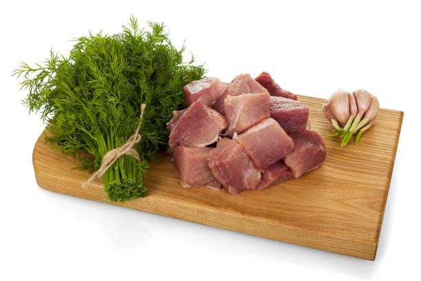 stücke von frischem schweinefleisch, bund dill und knoblauch auf schneidebrett isoliert auf weiss - schweinegulasch stock-fotos und bilder
