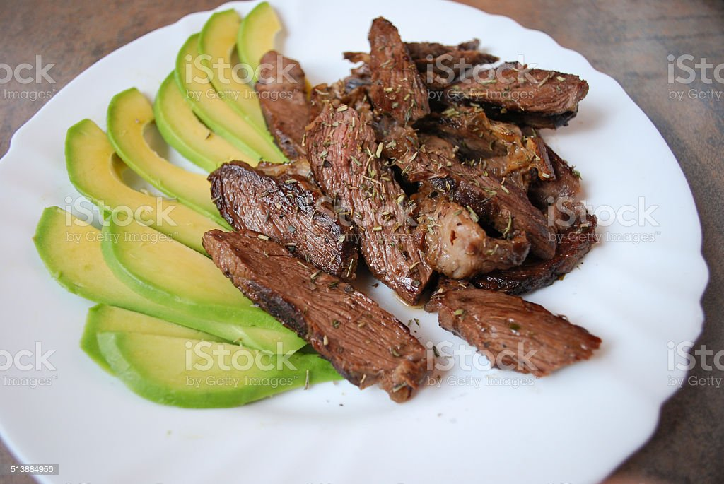 Pieces of grilled beef steak with avocado. stock photo