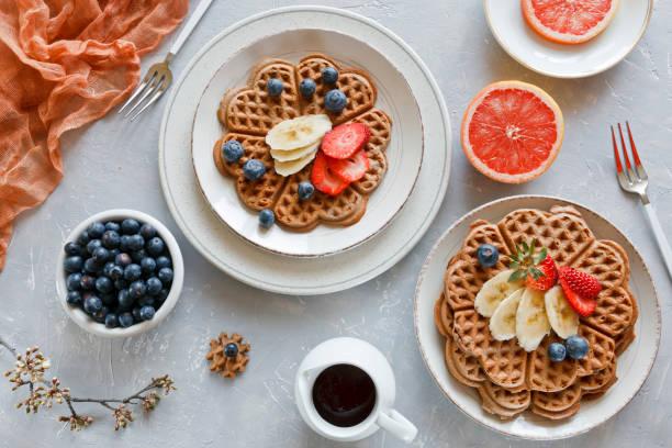Pedaços de bolo caseiro waffle com banana e blueberries sobre as placas no fundo cinza. Vista superior, close-up - foto de acervo