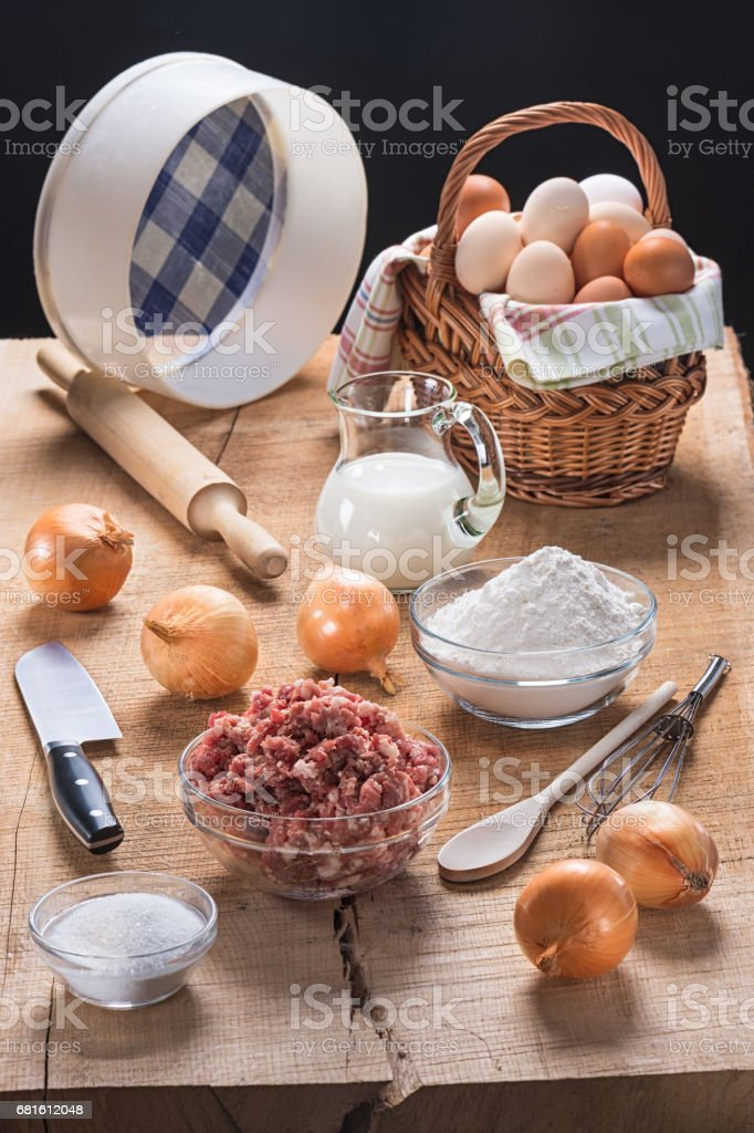 Pieces of kitchen utensils and a set of products for preparation of pelmeni and dumplings on an oak table-top стоковое фото