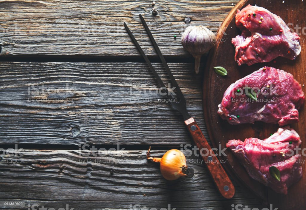 Pieces of meat, steak with spices on a wooden background. Food royalty-free stock photo